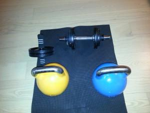Klar til træning på stuegulvet på kettlebells og håndvægte